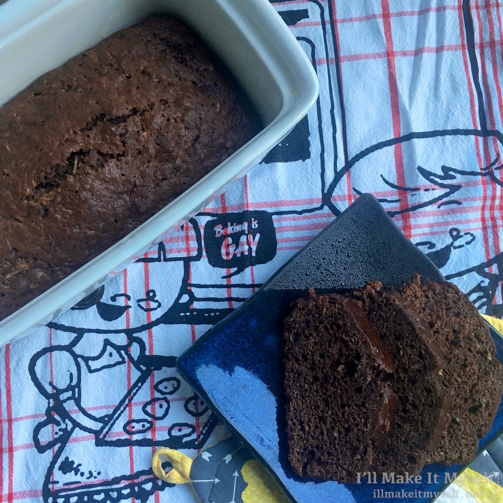 "Image of a loaf of chocolate zucchini bread and some slices of the bread on a ""Baking is Gay"" towel"