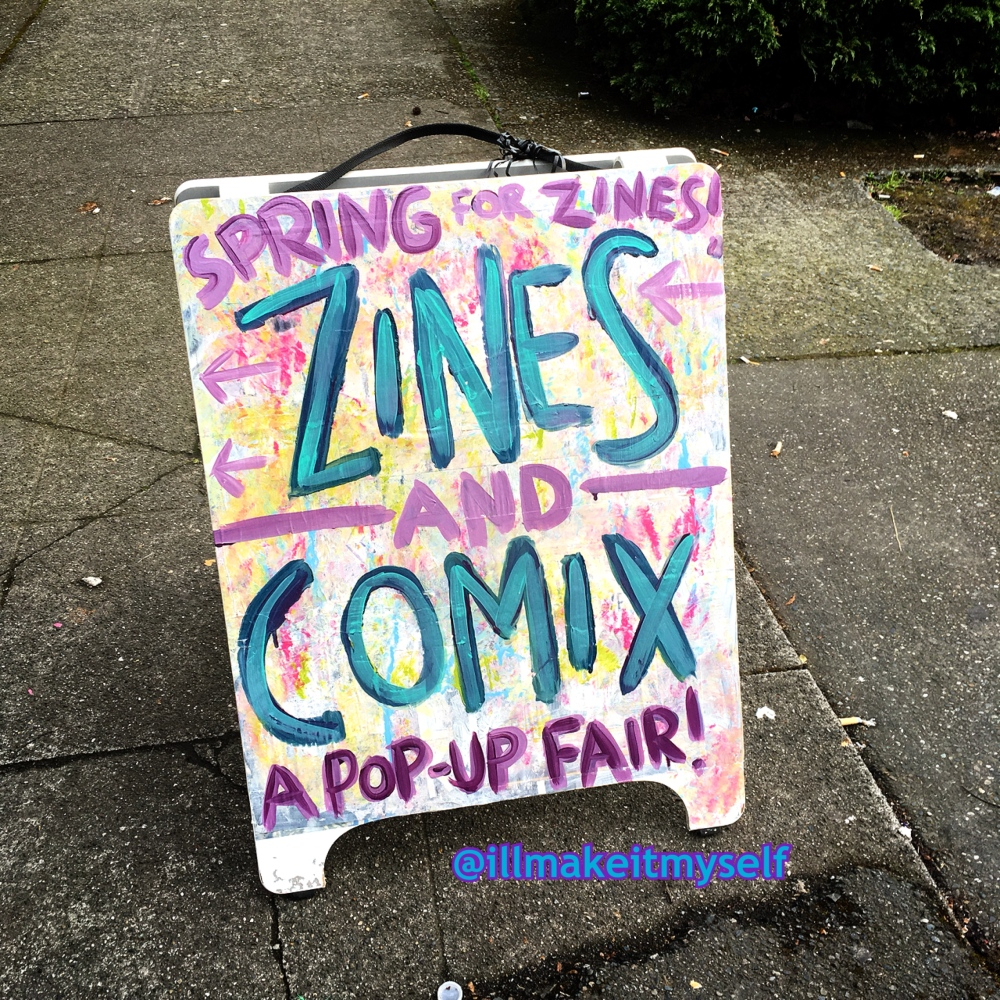 Image of a sandwich board with the text Spring for Zines! Zines and Comix: A Pop-Up Fair!