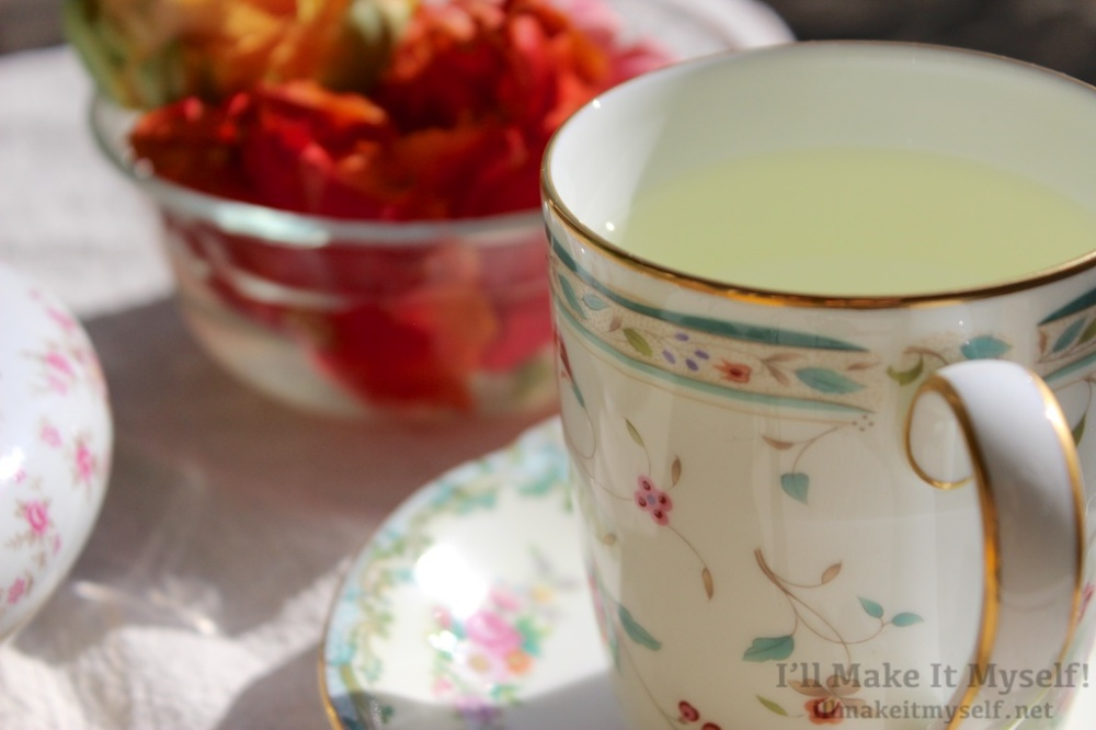 Image of a tea cup with a floral pattern and gold full of mint tea. The cup and saucer are on a table with red and orange ranaculus flowers in a bowl.
