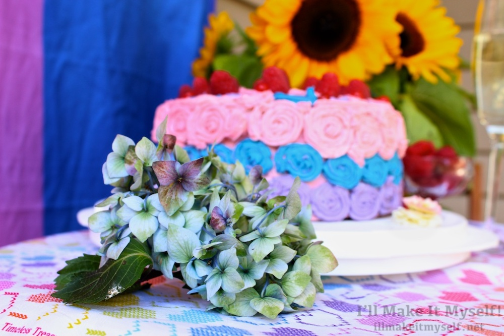 The cake with a blue hydrangea in the foreground and sunflowers in the background.