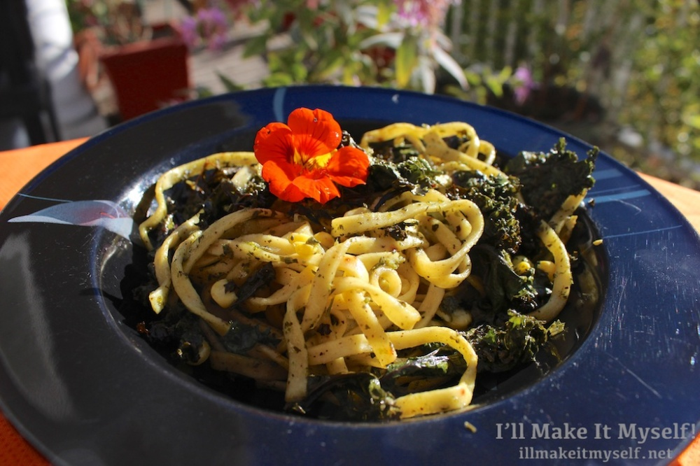 Image of pasta with pesto from recipe: egg noodles, roasted corn and kale, and a nasturtium on top.