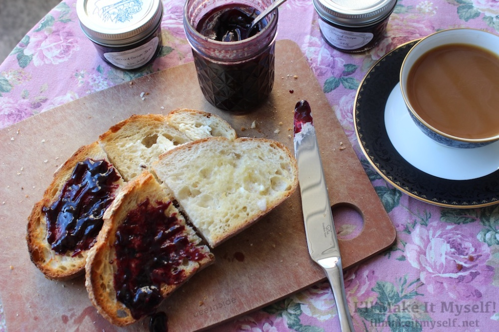 Image: two slices of toast on a cutting board. One half of each toast has purple jam on it and the other half has only butter. There are three jars of jam on the table; one is open and has a spoon in it. There is a cup of coffee in a porcelain cup with a saucer.