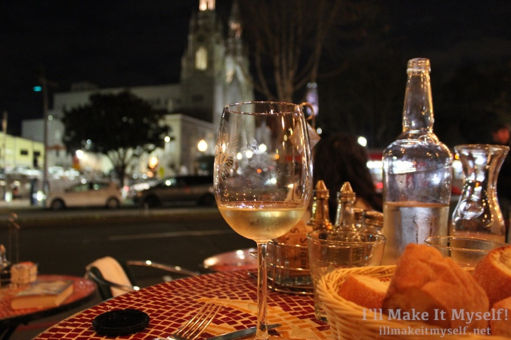 Image of a glass of white wine in the foreground with the view of the cathedral in the background.
