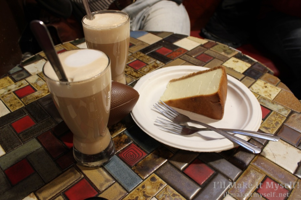 Image of a large piece of plain cheesecake with two forks, two lattes, and our mini football.