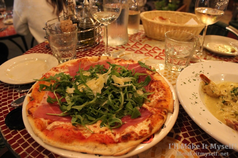 Image of pizza with prosciutto and arugula.