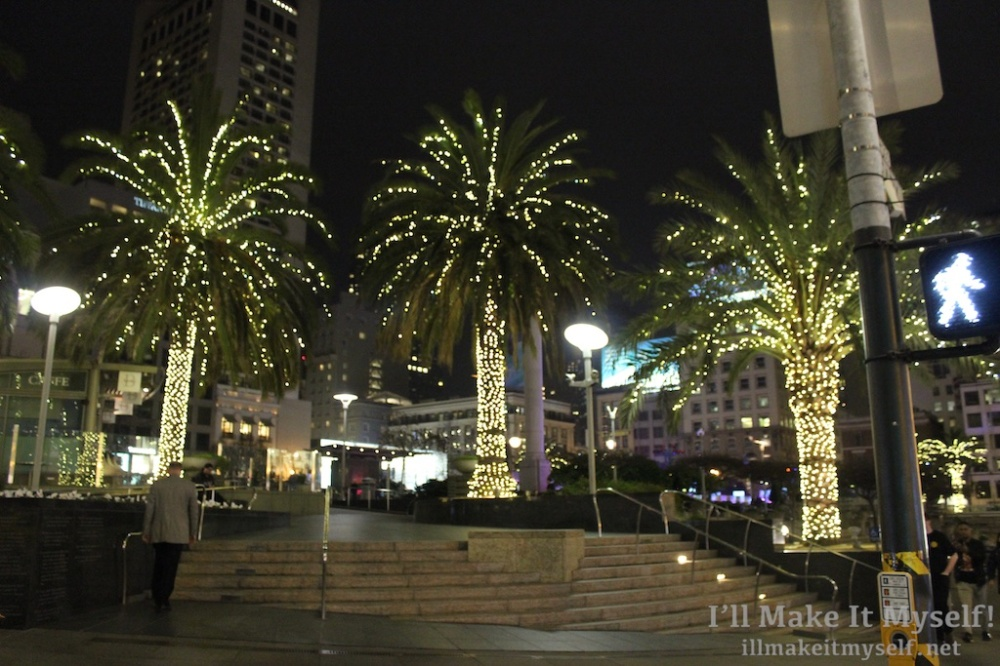 Image: Union Square, San Francisco. The stairs where Johnny walks past on the way to his surprise birthday party. This is a night scene. There are three palm trees with fairy lights on them.