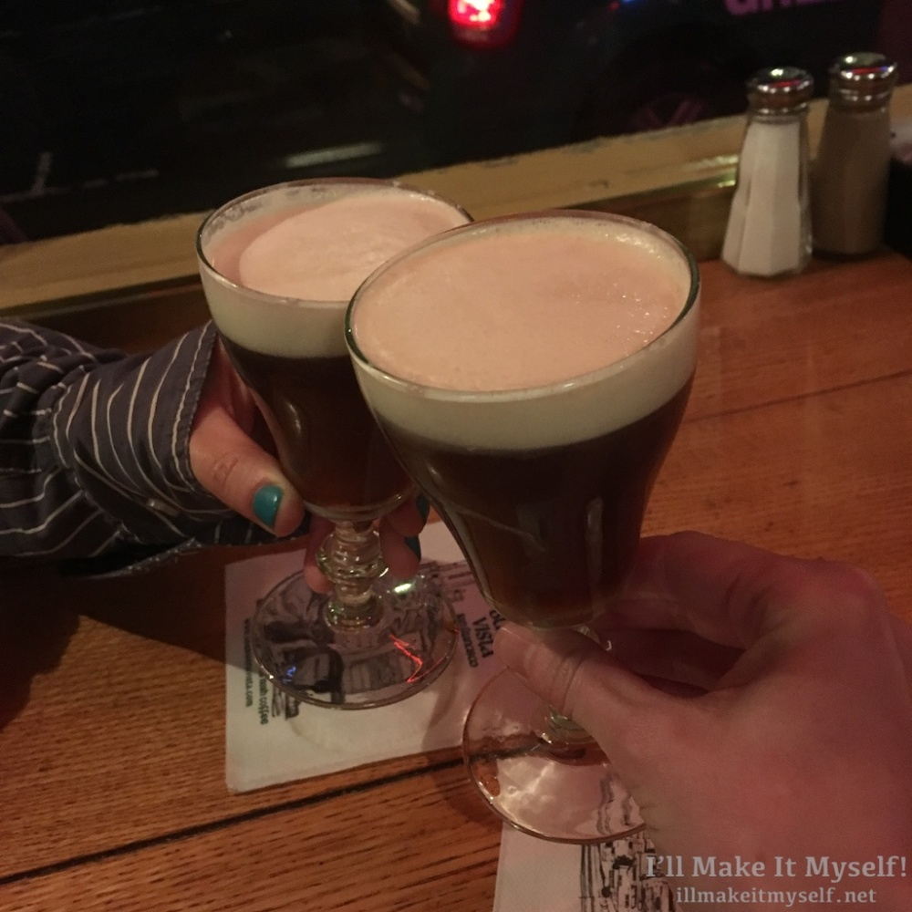 close up of Robin's and my hands toasting with our Irish Coffee.