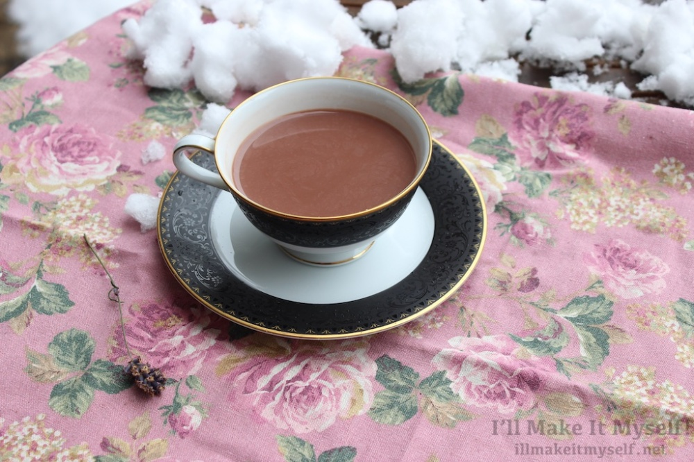 Image: a cup of hot cocoa in a black and gold Noritake tea cup and saucer. The background is a pink floral cloth with snow on it.