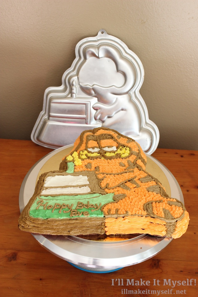 Image of the finished cake with its pan. The pan shows the outline of Garfield with the cake but has a flat blank spot where the eye piece would go.