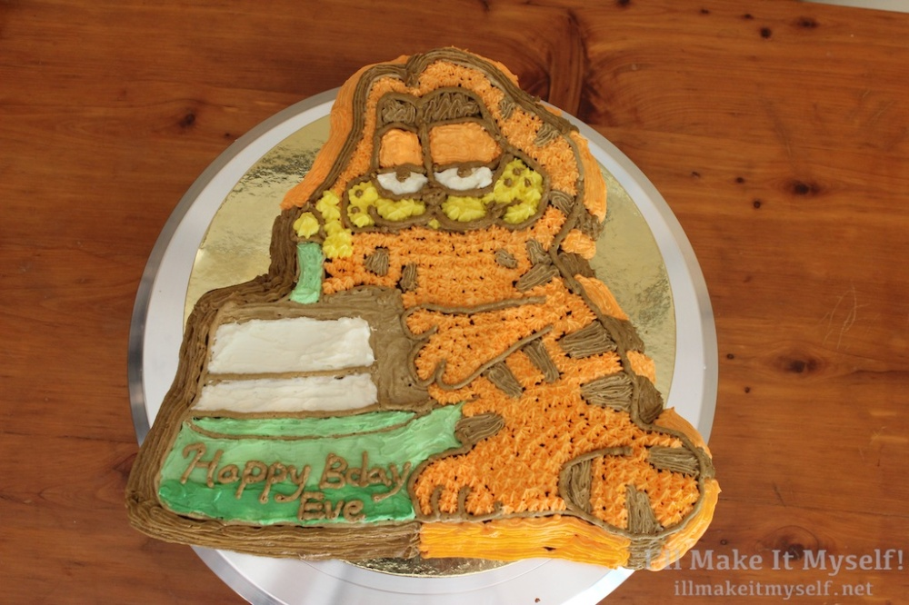 "Image of a 1980s Garfield-shaped cake, decorated. Garfield is an orange cartoon cat with stripes. The mold is designed to look like Garfield holding a slice of cake with a candle in it. The cake is decorated entirely in American buttercream. The stand under the slice says, ""Happy Bday Eve."""