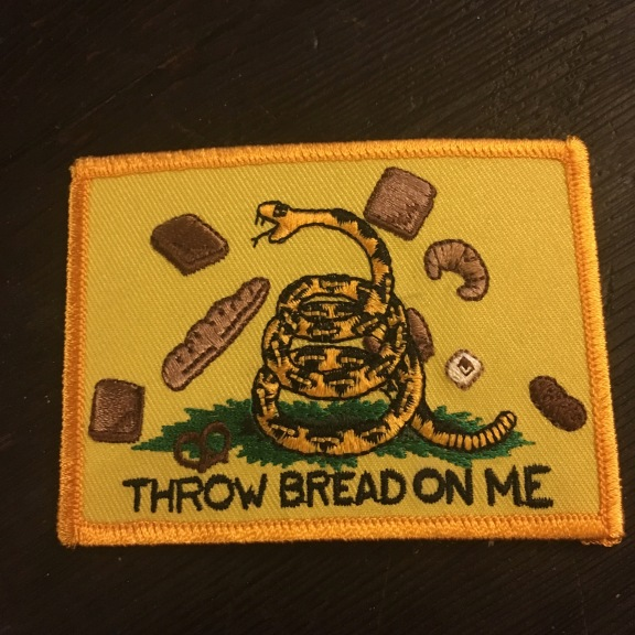 Image: a yellow embroidered patch with a picture of a snake and various types of bread. The text reads Throw Bread on Me, which is a reference to the Revolutionary slogan