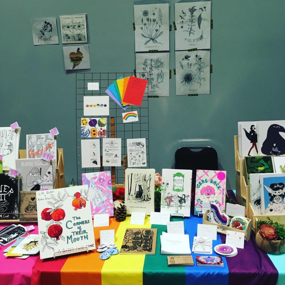The Corners of Their Mouth booth at Portland Zine Symposium. There is a rainbow flag on the table and copies of the Zines. There are large prints of botanical drawings.