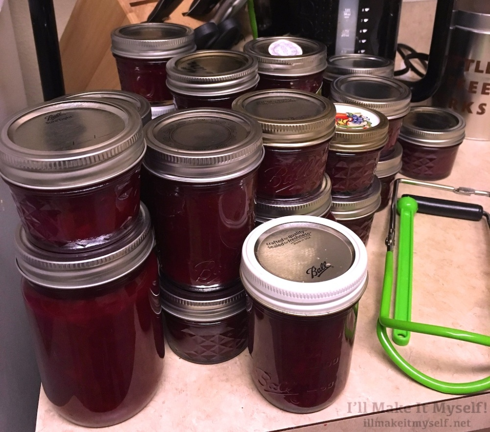 Many stacked jars of purple jam on our kitchen counter with the jam-jar tongs.