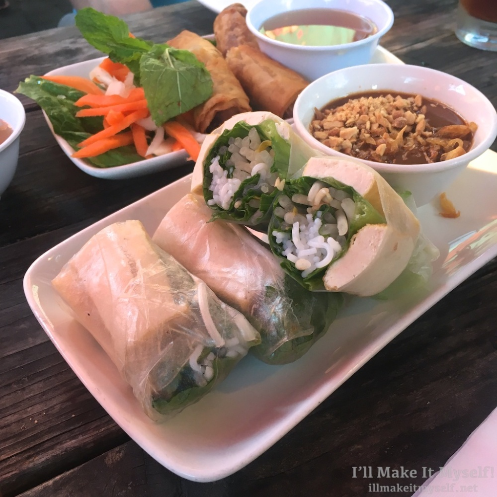A plate of spring rolls with tofu and peanut sauce on a wooden table.