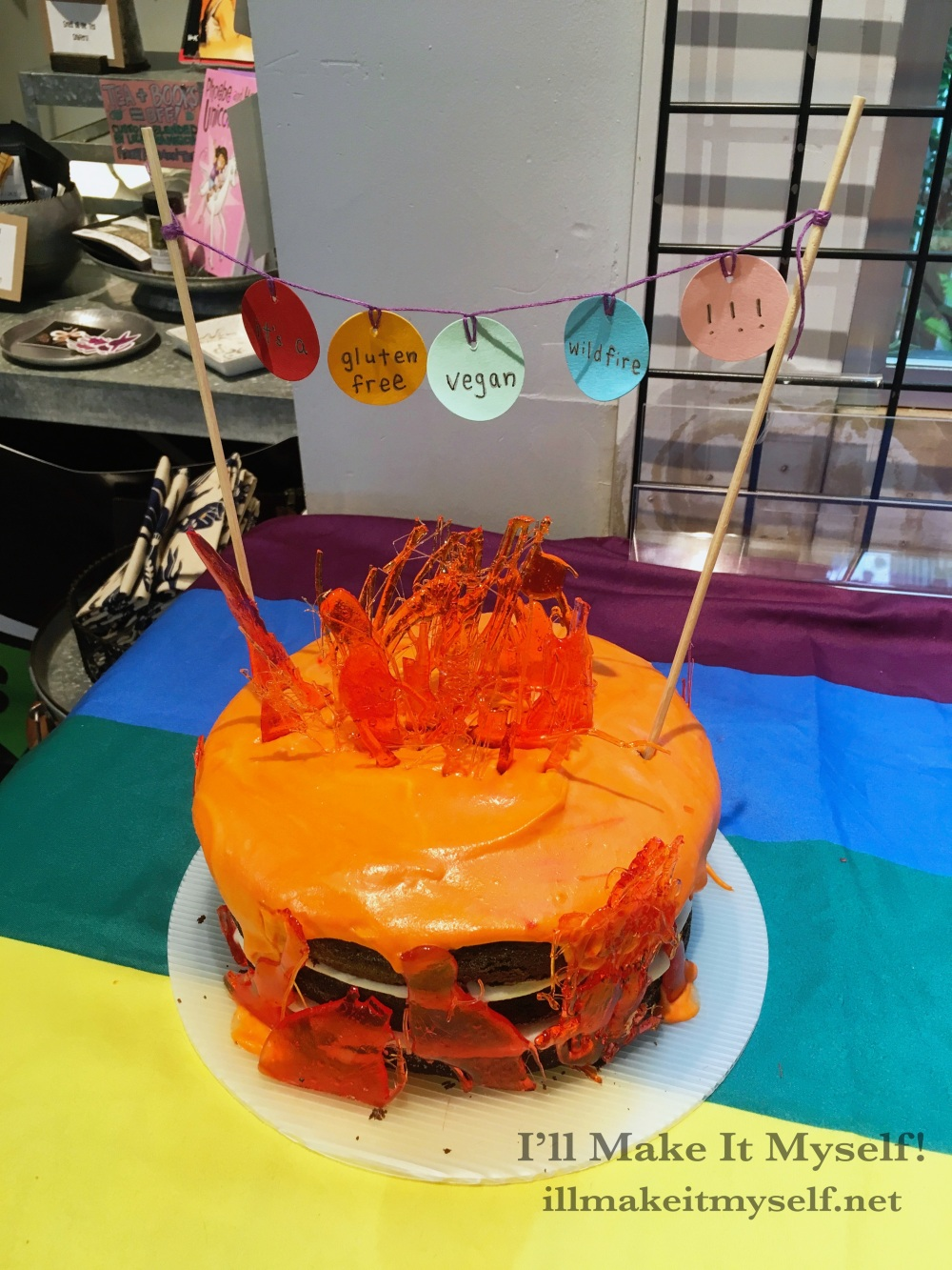 """Image: a shot from above of the 47,000 Gluten-Free Vegan Acre Wildfire Cake: a three-layer spicy chocolate gluten-free vegan cake. The cake has white coconut frosting between the bottom two layers and orange frosting on top dripping over the edges. There are orange and red flame-shaped candies pressed into the sides and top of the cake to look like flames. A mini-banner hangs between two skewers stuck into the cake. The banner reads, """"Congrats, it's a gluten-free vegan wildfire!!"""""""