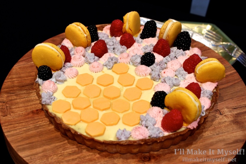 A custard tart with a honeycomb pattern in mango, with yellow macarons, blackberries and raspberries.