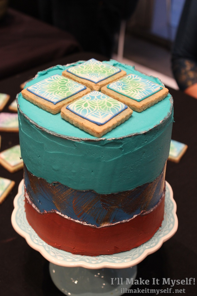 Detail of a layer cake. The top layers have vibrant turquoise frosting and four square cookies on top. The cookies have royal icing with a peacock feather design.