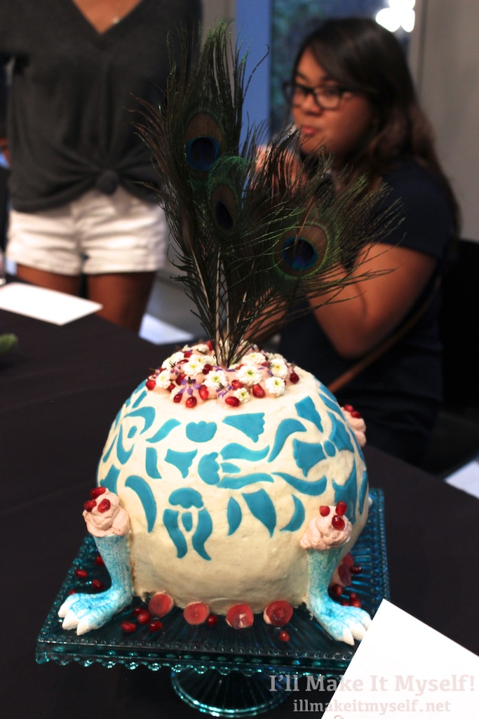 A cake carved into a round shape to resemble a vase. The outside is frosted white with turquoise tulip patterns and fondant turquoise bird feet. There are currants as decorations and peacock feathers on top.