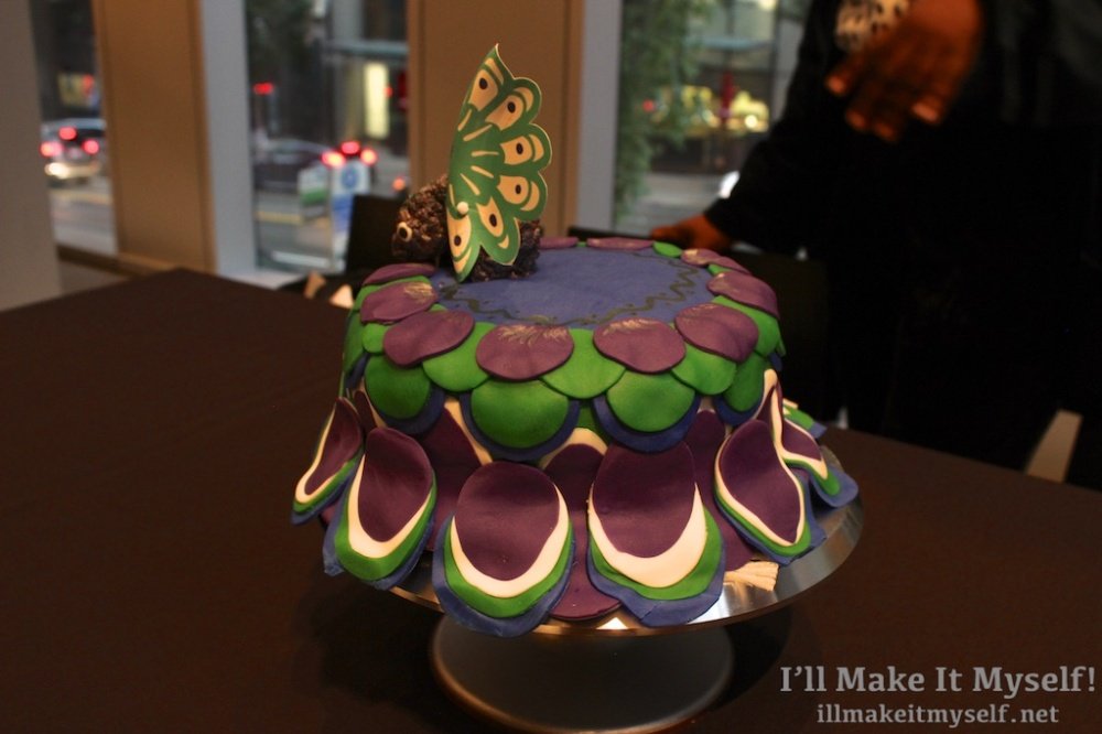 Image of a layer cake with peacock feathers made of fondant n navy, green, white, and purple.