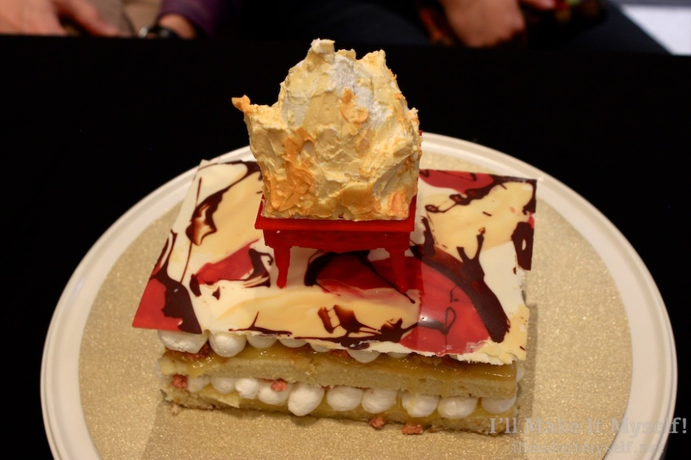 "A rectangular cake in layers filled with buttercream. The top of the cake is a flat piece of chocolate work in red, yellow, brown, and white swirled. The top is a sculpted fondant brazier with marshmallow ""flames."""