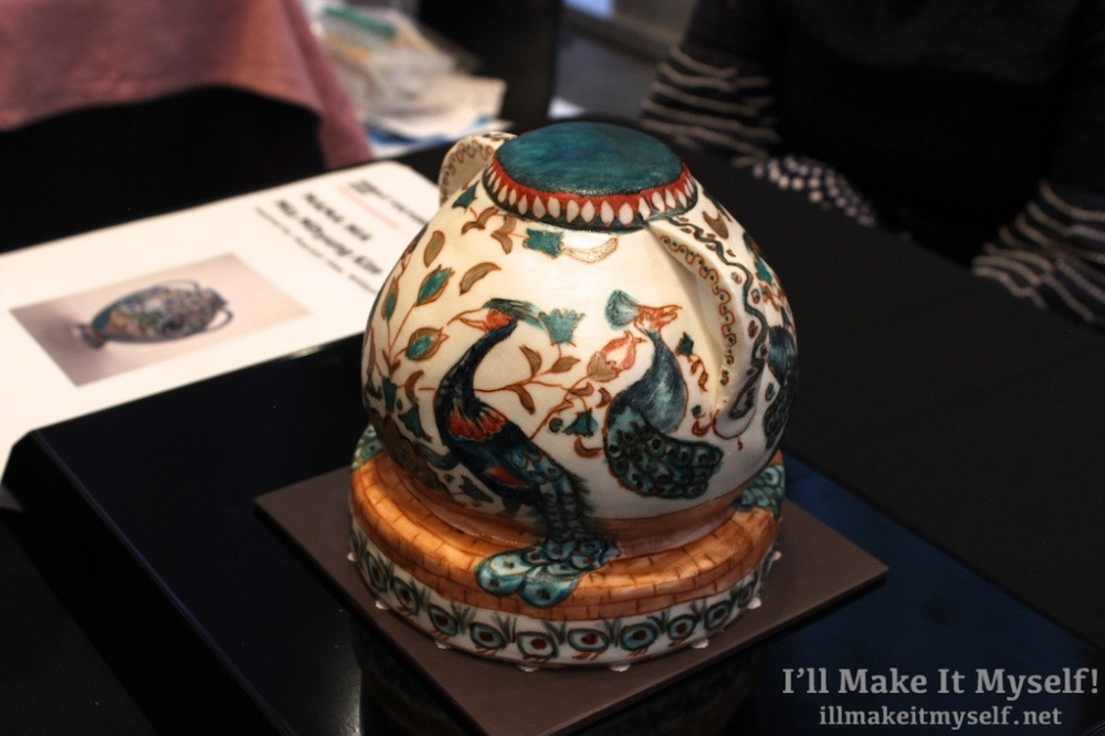 A cake sculpted to look like a round vase. The outside is covered in white fondant, which is painted to look like a vase with colorful peacocks on it.
