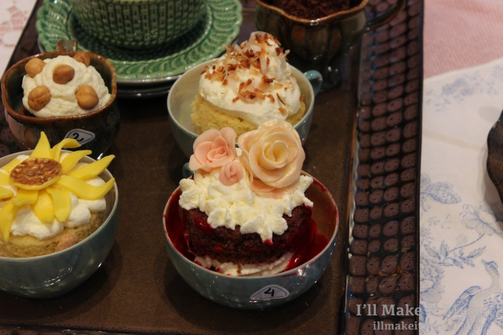 Close up of tea cakes set in tea cups. The cakes are decorated with frosting flowers (roses and sunflowers).
