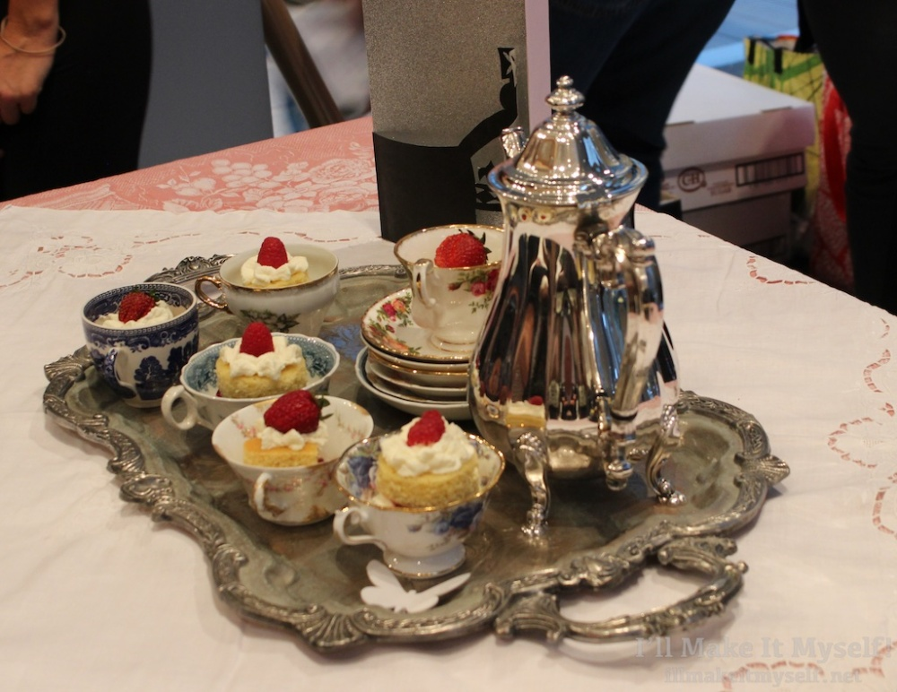A silver tea set with tea cakes decorated with cream and strawberries.