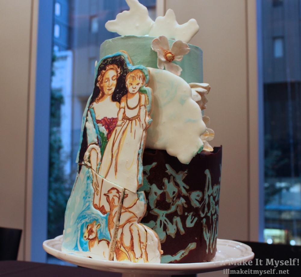 A two tiered cake with a turquoise buttercream on top and a chocolate collar with turquoise accents on bottom. There is a cake propped against the cakes painted to look like a mother holding a short-haired blond child in a long gown to see lambs in a field.