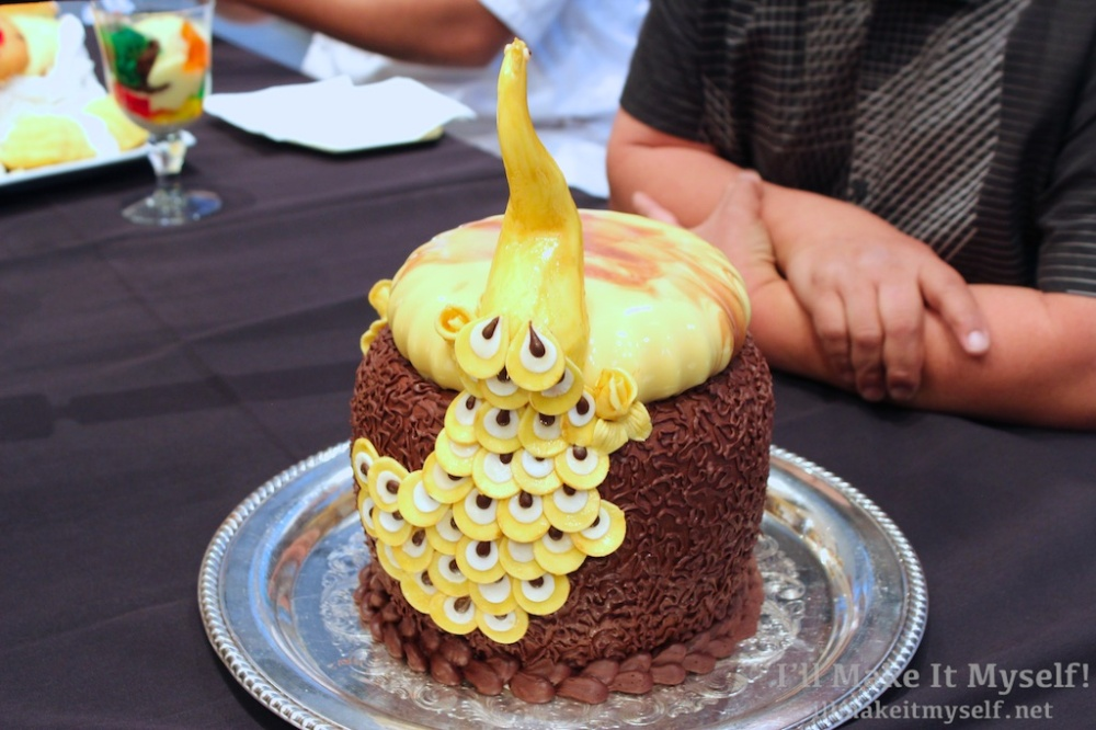 A chocolate layer cake with chocolate shavings on the side. A yellow peacock made of fondant and a passionfruit curd jelly on top.