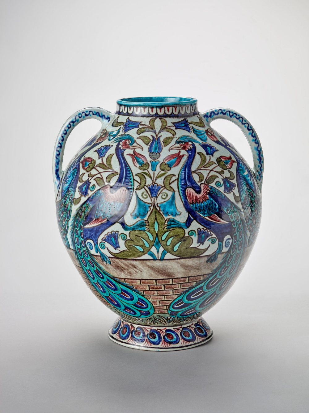 A two-handled clay vase glazed with an elaborate pattern with two peacocks in blue, cerulean, olive green and red.