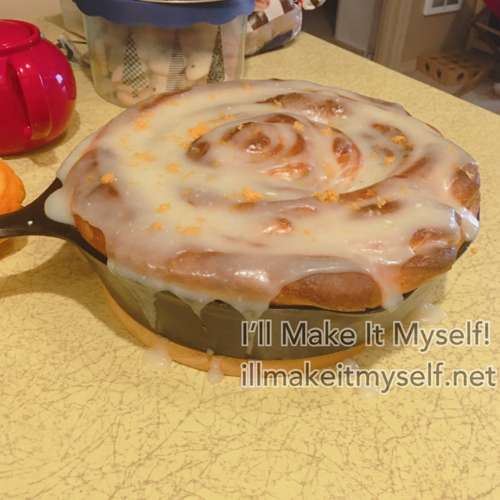 A huge cinnamon roll topped with too much frosting and some orange zest, on top of the yellow formica table. Tea pot for scale.