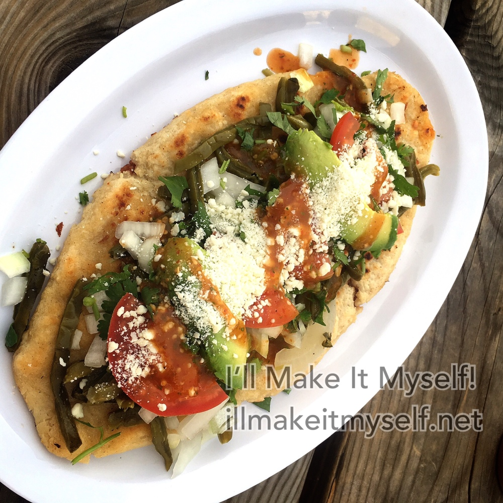 Tlacoyos on a paper plate. The tortilla is stuffed with beans and topped with cilantro, cheese, vegetables, and tomatoes.