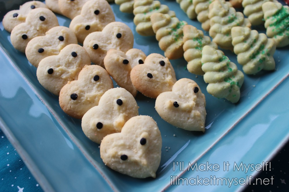 "A teal rectangular tray of cookies. Close up of the owls: white heart shapes decorated with black confetti ""eyes."""