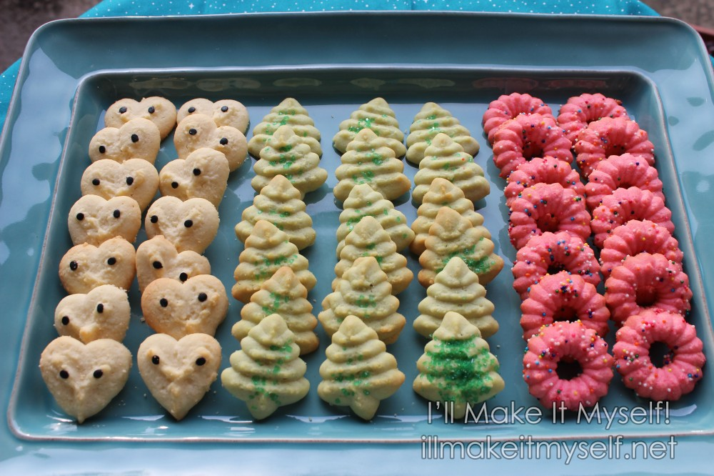 A teal rectangular tray of cookies. There are three kinds of cookies: white heart shapes decorated with black confetti