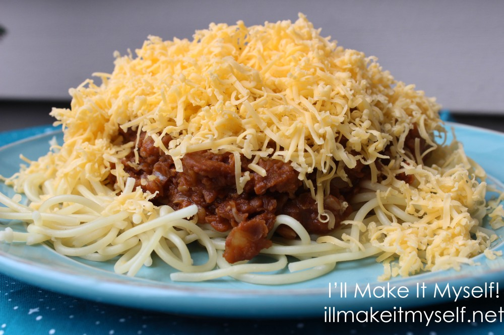 A plate of vegetarian Cincinnati chili with red lentil chili sauce. The chili is on top of spaghetti and covered with a mound of cheddar cheese. The plate is on a blue cloth with a star pattern from Fireside Textiles.