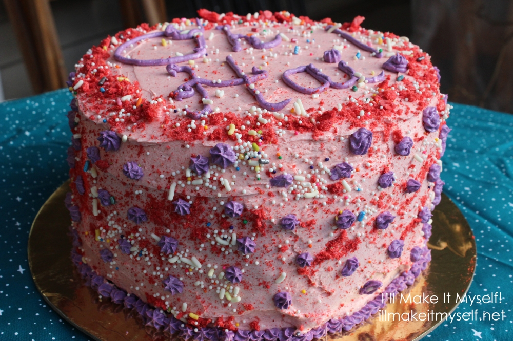 "Side view of the cake. A three-layer cake frosted in pink buttercream. There is a dusting of crushed freeze-dried strawberries around the edge of the top layer. The cake is covered in rainbow ball sprinkles and jimmies. There is text on the cake in purple icing: ""Oh Hai!"" There are also purple stars piped on the sides and the edge of the bottom layer. The cake is on a gold cake round on a blue cloth with white stars."