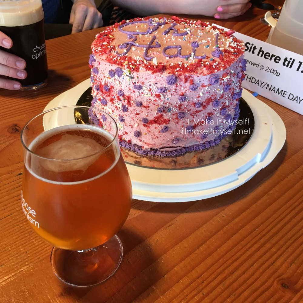 "A three-layer cake frosted in pink buttercream. There is a dusting of crushed freeze-dried strawberries around the edge of the top layer. The cake is covered in rainbow ball sprinkles and jimmies. There is text on the cake in purple icing: ""Oh Hai!"" There are also purple stars piped on the sides and the edge of the bottom layer. The cake is on a gold cake round on a white cake carrier bottom. There is a glass of beer (Optimism) on the table with ""Birthday/Name Day"" on the reserveration placard. Someone is holding another glass of dark beer in the background."