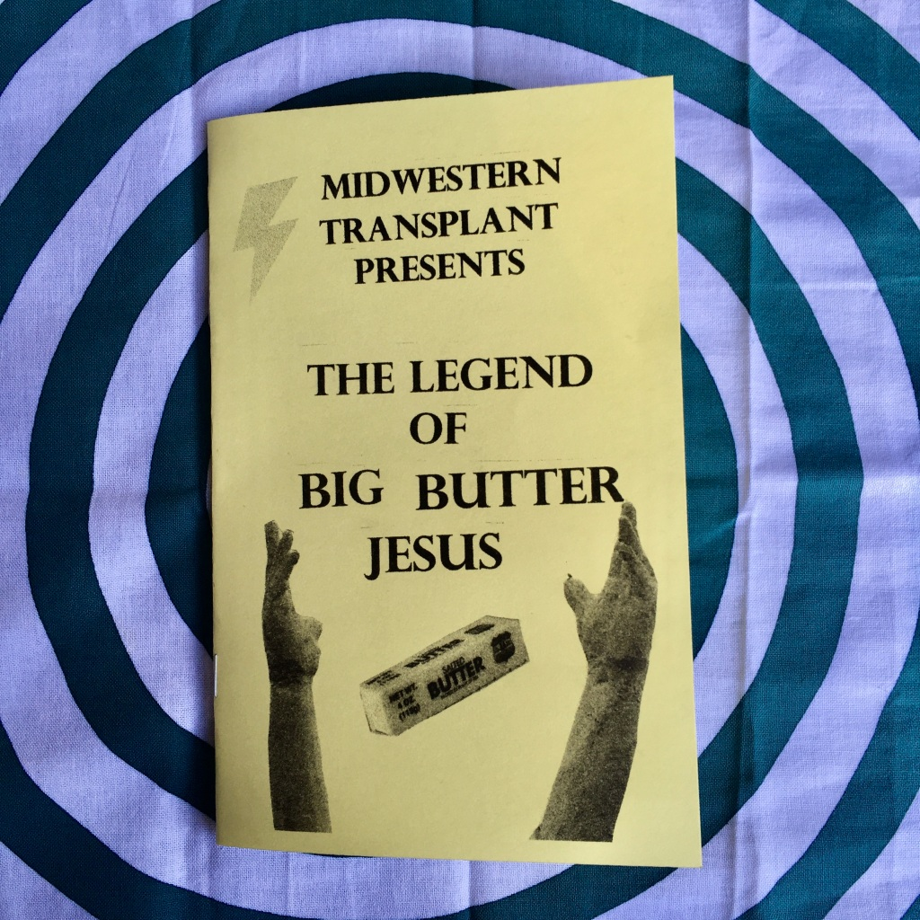 A photograph of the cover of Midwestern Transplant Presents The Legend of Big Butter Jesus: a yellow folded zine. Along with the text, the zine cover features a clip-art lightning bolt, a stick of butter, and the hands of the King of Kings Jesus statue reaching up in the air.