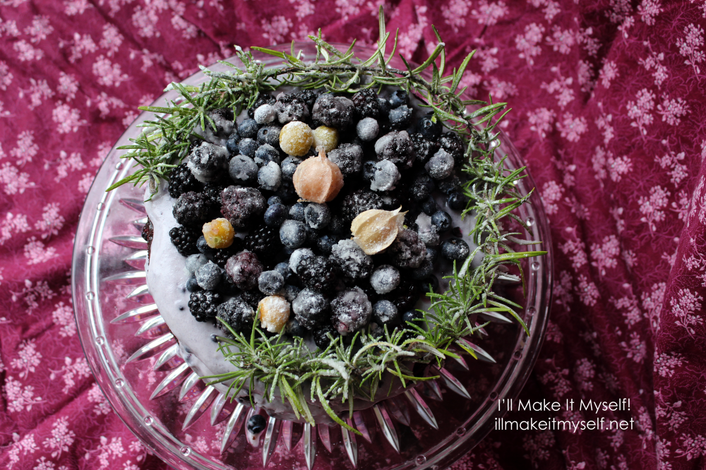 Goblin Market Cake: a two-layer chocolate cake on a crystal cake stand. The cake is frosted in a light-purple coconut whipped cream and topped with sugared rosemary in a semi-circle and sugared blackberries, blueberries, and yellow ground cherries. Overhead view.