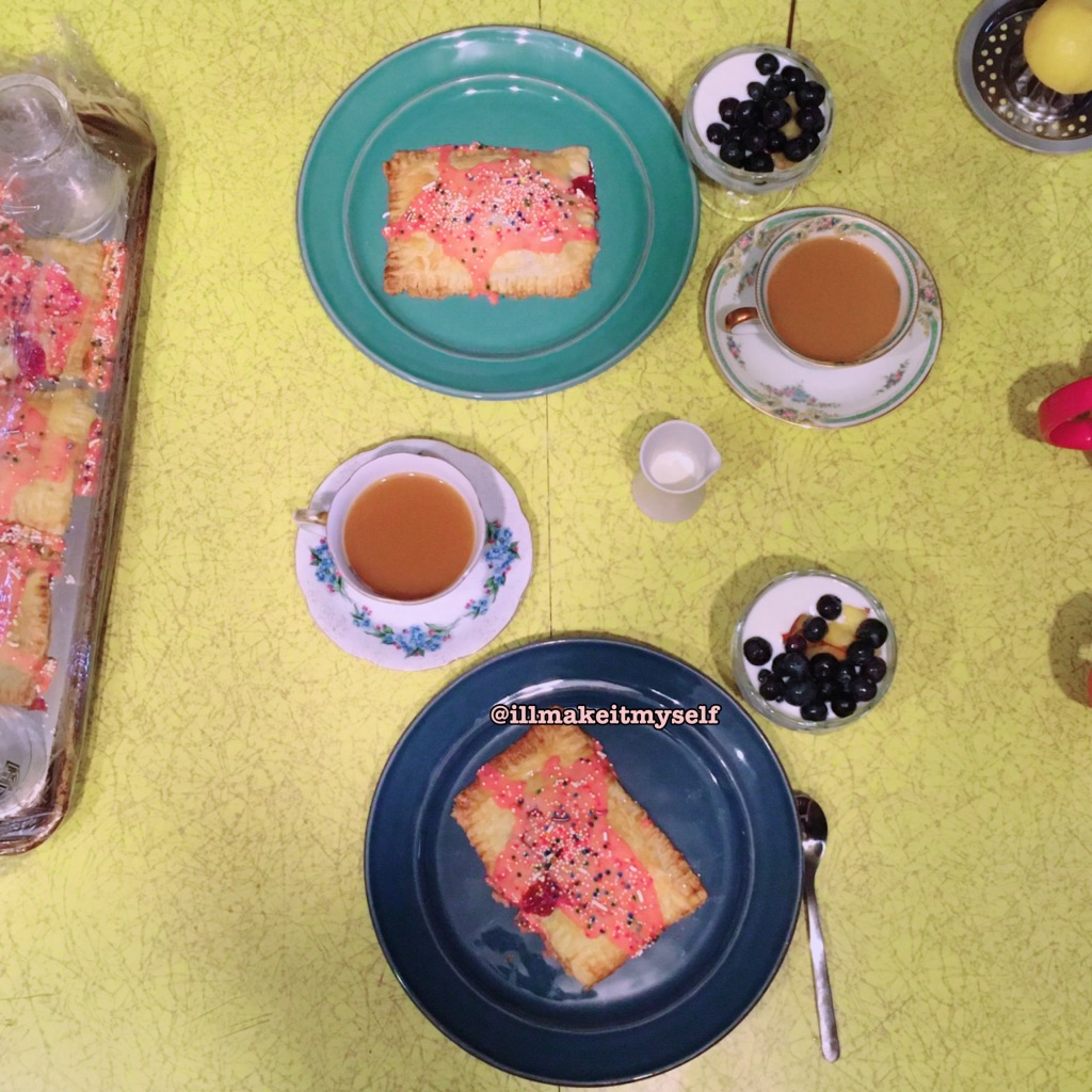 An overhead photo of two plates with homemade strawberry poptarts, yogurt and blueberries, and china teacups and saucers with coffee.
