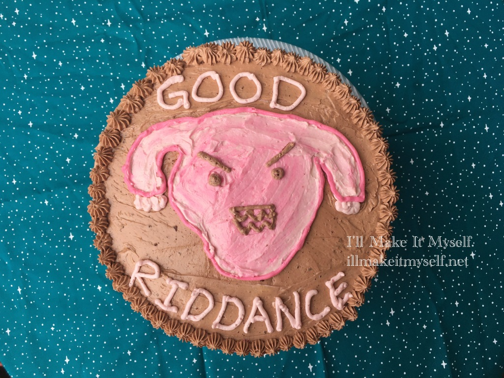 """overhead photo of a chocolate layer cake. The frosting is chocolate. There is a design of an angry cartoon uterus in pink raspberry frosting on the today, and """"Good Riddance"""" is piped on in pink frosting."""