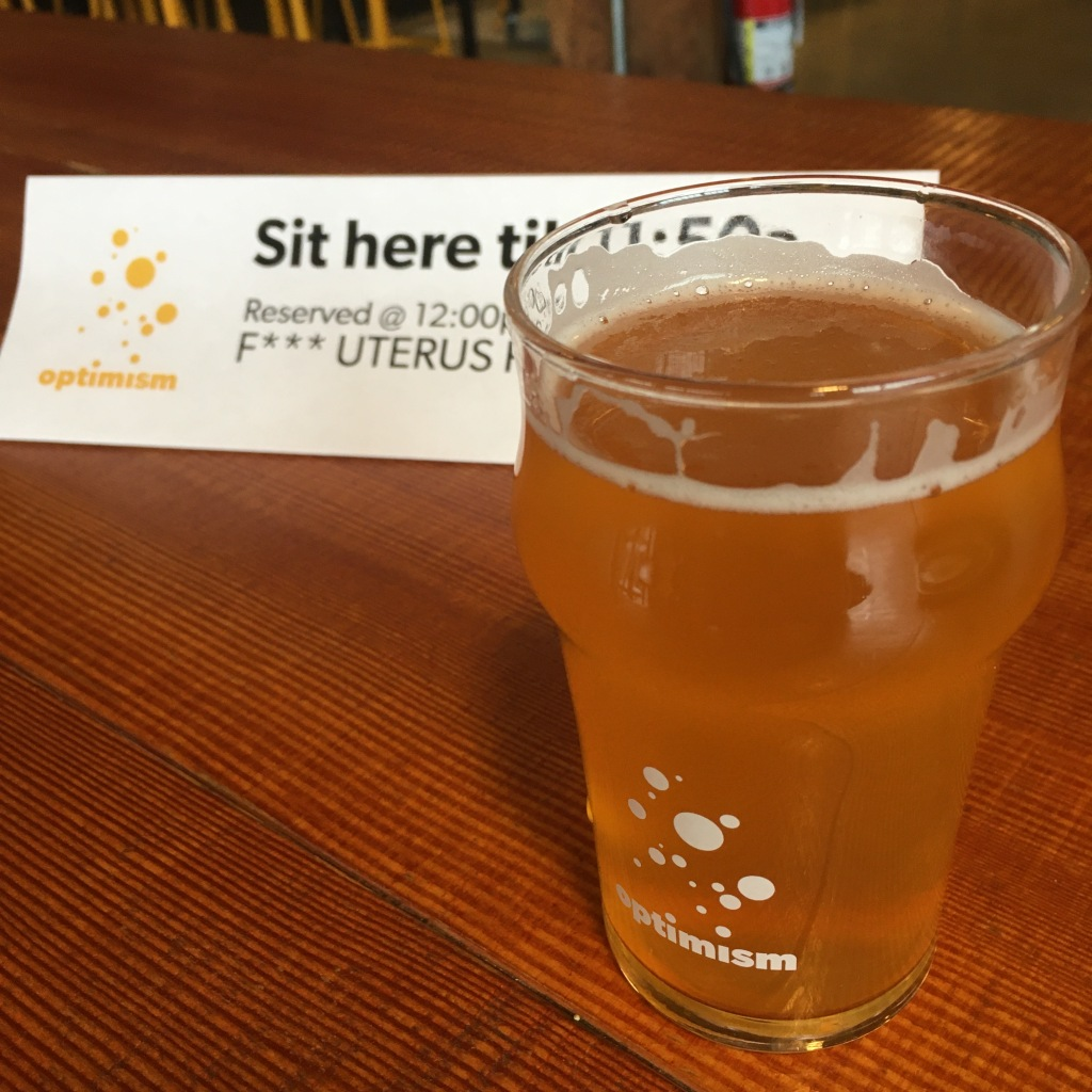 """Photo of a small glass of beer in an Optimism Brewing glass in front of a placard that reads """"Sit here till 11:50 am. Reserved at 12 pm for F*** Uterus Party."""""""