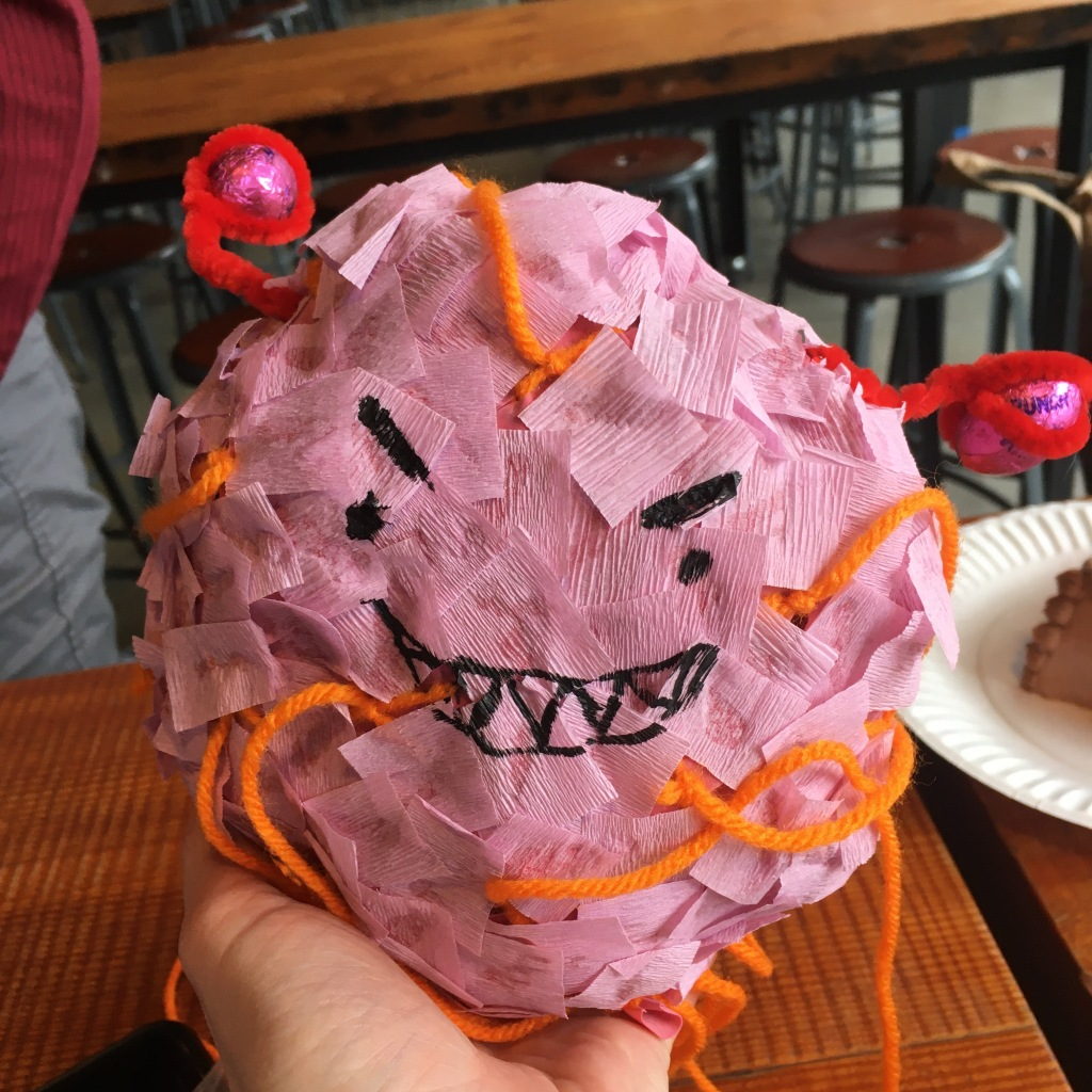 """A whoopie cushion covered in pink crepe paper with a sharpied angry smile. There is orange yarn to pull apart the """"piñata."""" The fallopian tubs are red pipecleaners with chocolates wrapped in pink wrappers for the ovaries."""