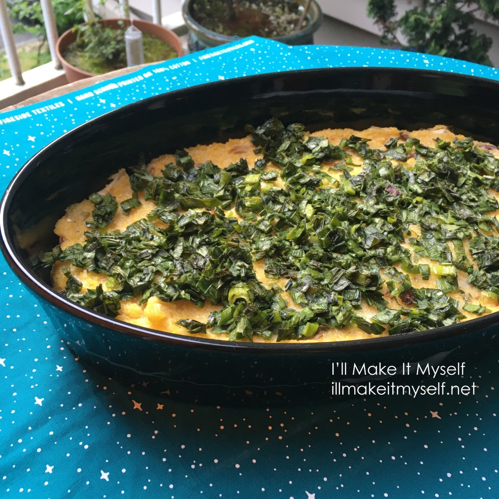 Polenta casserole topped with sauteed green spring onion stems. The casserole is in an oval black casserole dish and is on top of a piece of turquoise fabric with a starry sky pattern.