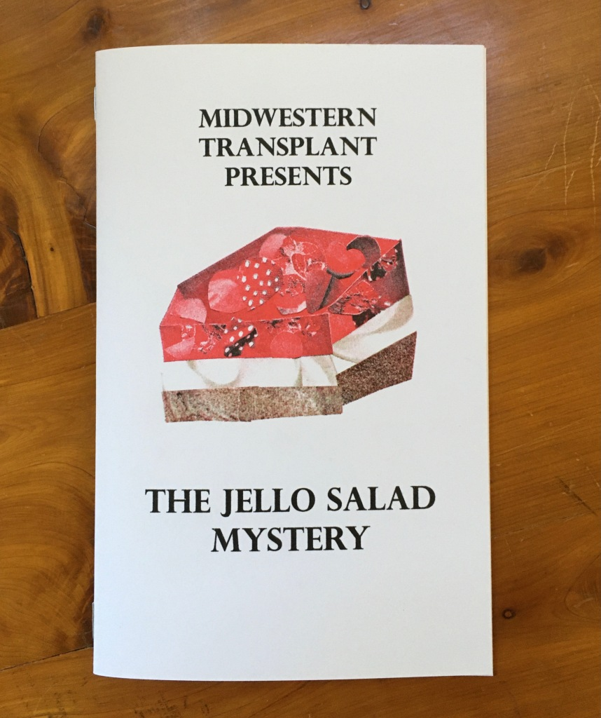 """Image of the cover of Midwestern Transplant Presents: The Jello Salad Mystery. The cover is digest size (5.5"""" x 8.5"""") and features the text above with a risograph printed collage image of a Strawberry Pretzel Salad. This dessert is a layered jello dessert that has a top layer of red strawberry jello and strawberries, white middle layer of whipped cream/whipped topping and cream cheese, and a bottom layer of pretzel crust."""